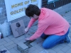 Board member Lynna Thomas removed bricks to place the Murphy family 12″ x 12″ paver.